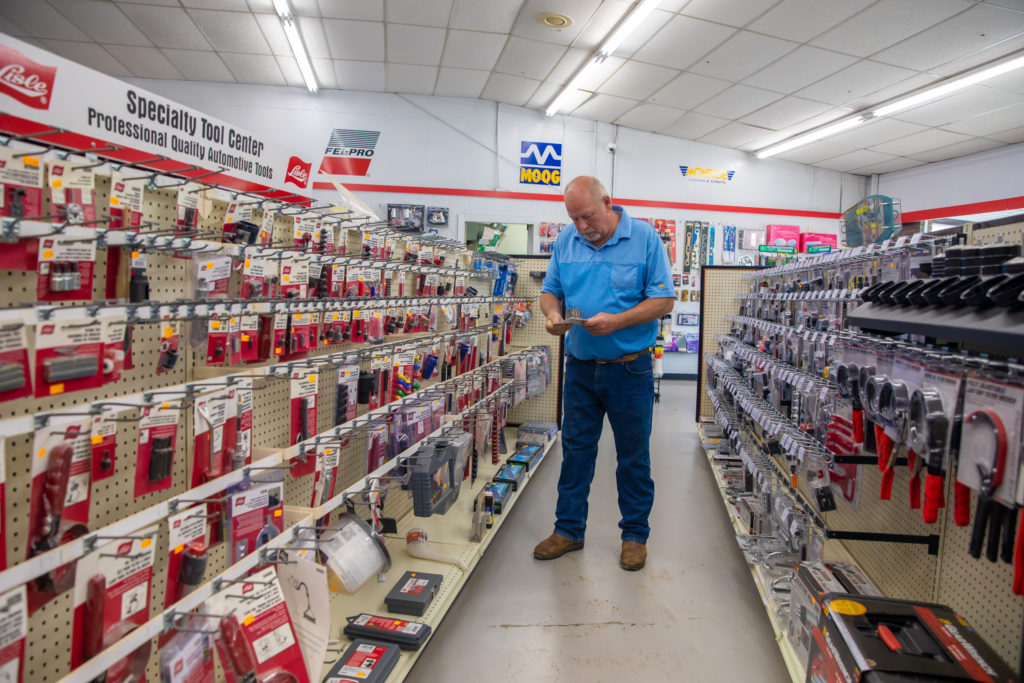 customer in an auto parts store looking at an item in the middle of a shopping aisle